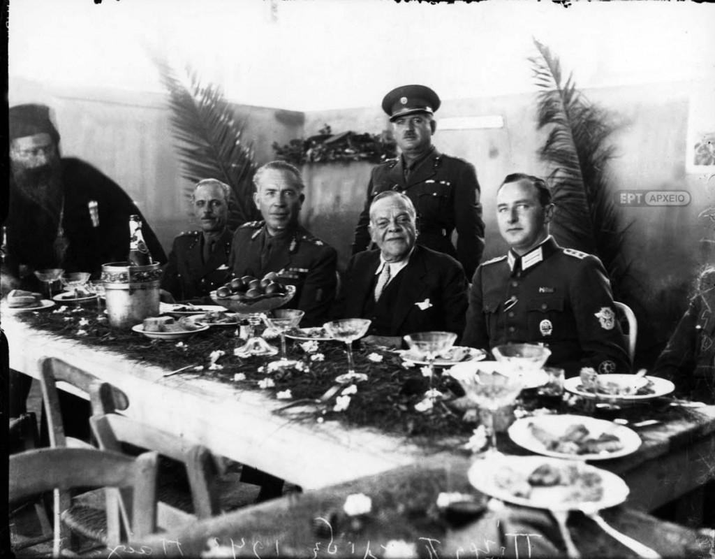 Ο διορισμένος από τις γερμανικές αρχές Κατοχής πρωθυπουργός Ιωάννης Ράλλης σε πασχαλινό γεύμα. Δεξιά του ο αντισυνταγματάρχης Βασίλειος Δερτιλής, διοικητής των Ταγμάτων Ασφαλείας και αριστερά του ο Γερμανός αξιωματικός Φίσερ, Αρχείο ΕΡΤ – Πέτρος Πουλίδης