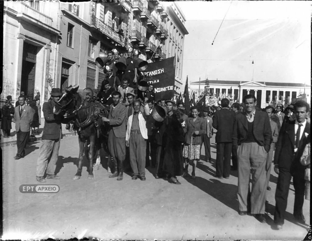 Εορτασμοί για την Απελευθέρωση. Μέλη του ΚΚΕ στη συμβολή των οδών Πανεπιστημίου και Κοραή. Κρατούν σημαίες και πανό και φωνάζουν συνθήματα χρησιμοποιώντας το χωνί, Αρχείο ΕΡΤ – Πέτρος Πουλίδης