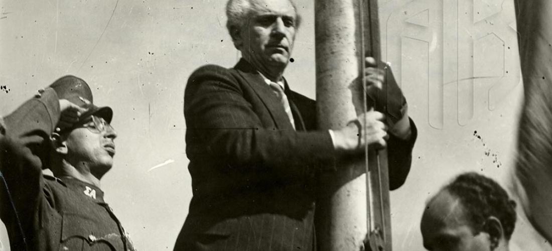 18 Οκτωβρίου 1944. Ο πρωθυπουργός Γεώργιος Παπανδρέου κατά την πρώτη ελεύθερη έπαρση της ελληνικής σημαίας στην Ακρόπολη, Γενικά Αρχεία του Κράτους – Κεντρική Υπηρεσία –  Βασίλης Τσακιράκης